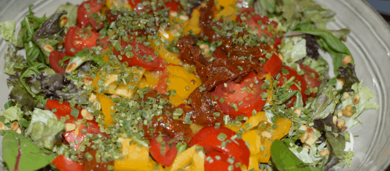 Salade rucola zongedroogde tomaten pijnboompitten